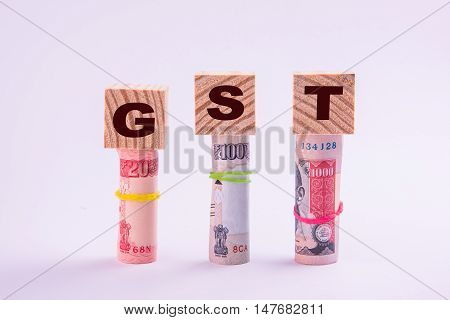 wooden cubes with GST text written over it placed over 3 rolls of indian currency notes, isolated over white background