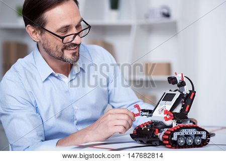 Good mood. Middle-aged white man in glasses fixing a small robot.