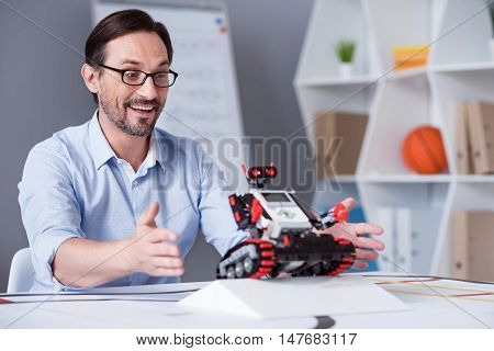Everything works Middle-aged white male turning a machine on while performing an experiment