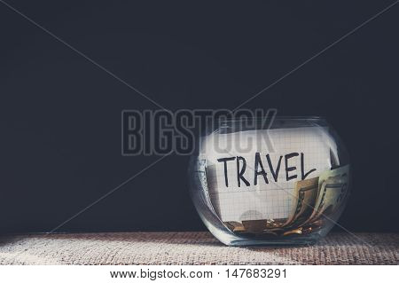 Jar labeled travel filled with money and coins