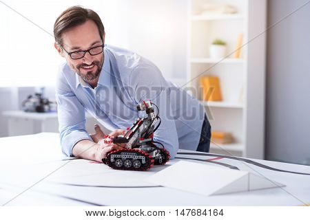 Passionate with work. Attractive man in glasses working on droid creation