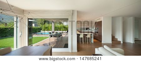 Luxury home interior, wide open space, veranda and garden view from the windows