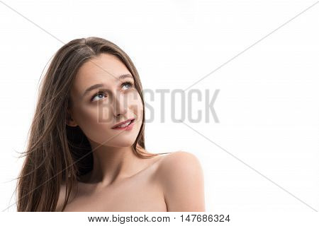 Dreamful young girl is standing and looking up pensively. She is biting her lip with desire. Isolated and copy space in right side
