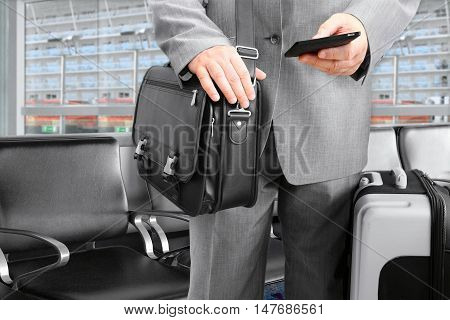 Traveling Businessman with His Luggage Using Phone at the cruise terminal