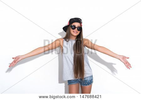 I am happy. Joyful hipster girl is standing and stretching arms sideways. She is laughing. Isolated