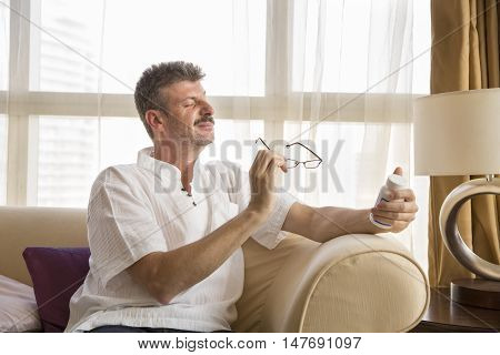 middle aged man trying to read the lable on medicine bottle