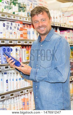 Man Reading Label On The Bottle In Supermarket