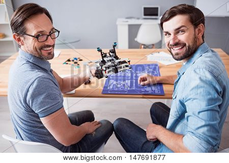 Glad to work together. Cheerful delighted professional colleagues sitting at the table and smiling while holding robot