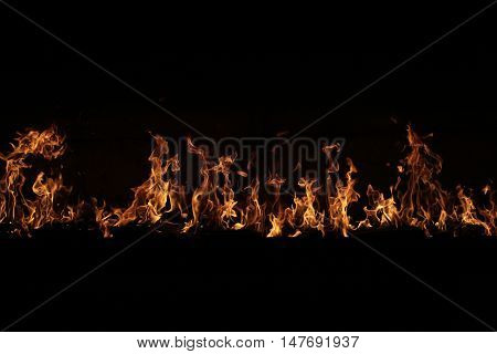 fire line on black. Shining flame on dark background. A lot of space for text. Copy space. Flaming line made of orange fire