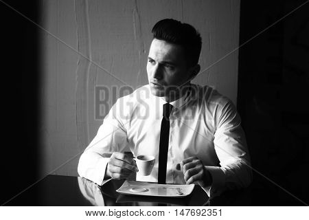 Man young handsome elegant model wears shirt skinny necktie sits at table holds cup of coffee and looks away indoor black and white on grey background