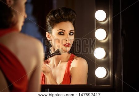 Confident young woman is doing make-up backstage. She is touching powder brush to chin. Model is sitting and looking at mirror with seriousness