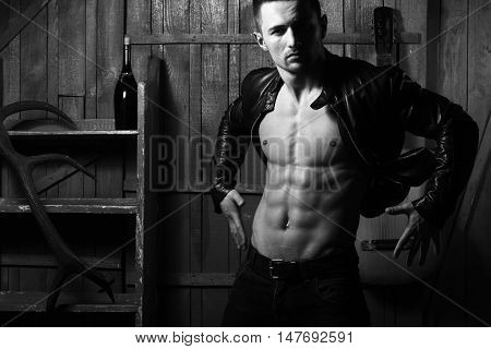 Handsome young man with sexy muscular bare torso in leather jacket standing with acoustic guitar wine bottle and antler on wooden background black and white