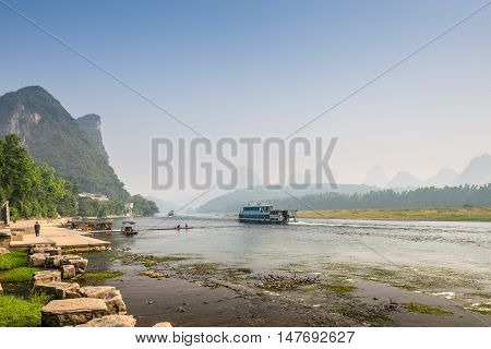 Yangshuo China - October 22 2013: Pier for boats in the tourist town Yangshuo on the banks of Li river in China. Li river flows 83 kilometres from Guilin to Yangshuo with surrounded by karst mountains as a highlight.