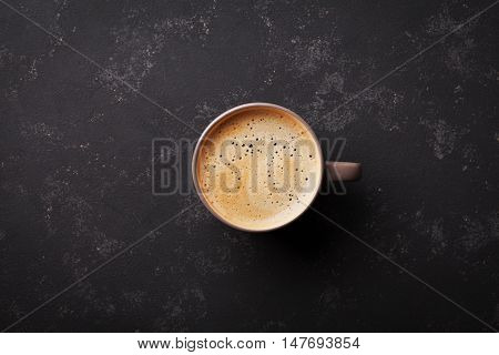 Cup of fresh coffee on vintage black table, top view, flat lay.
