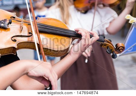 young musician playing the violin on the streets of a city