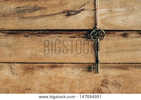 Old Key Hanging On Brown Wood With Space.