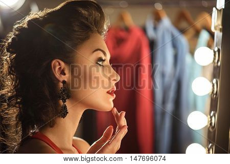 Confident female model is smartening herself up backstage. She is touching her chin gently. Girl is sitting and looking at mirror with serenity