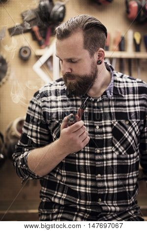 Environmental portrait of a young adult craftsman sitting and smoking a pipe tobacco in a workshop for wood work and construction.