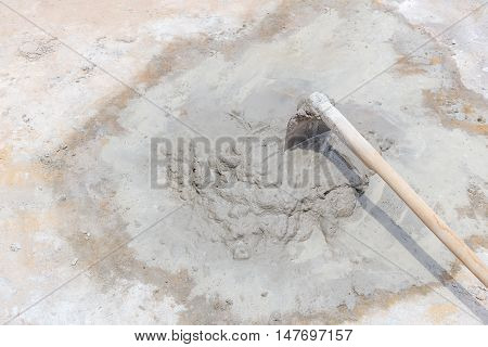old hoe with cement mixed on concrete floor