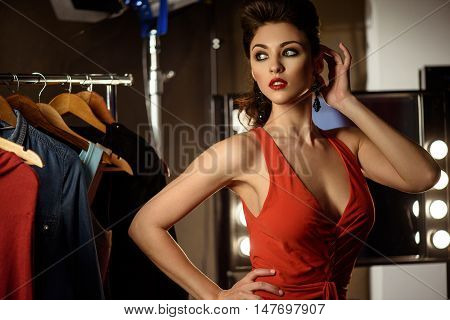 Attractive female model is standing in dressing room and posing. She is looking aside with desire