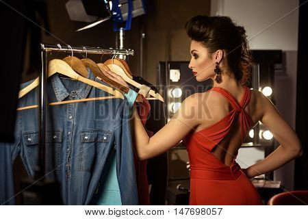 Confident young woman is taking fashionable clothing from rack in dressing room. She is looking forward with passion and posing