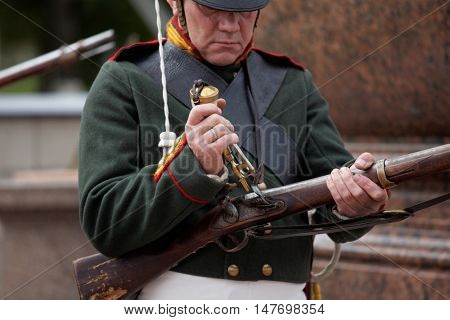 GATCHINA, ST. PETERSBURG, RUSSIA - SEPTEMBER 10, 2016: Soldier in retro uniform of Russian Army loads the gun on the platz in front of Gatchina palace during the festival Gatchinskaya Byl
