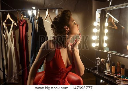 Pretty female model is applying make-up on her face. She is touching chin and looking at mirror with concentration. Girl is sitting near hanging clothing backstage
