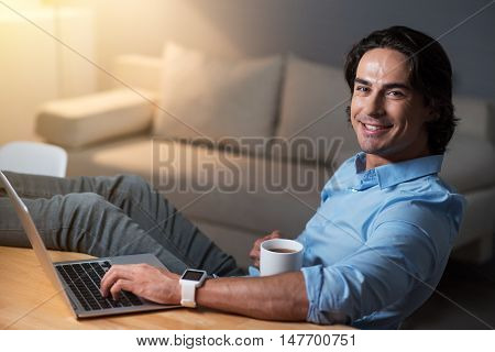 Few minutes for rest. Handsome glad young man drinking tea and using laptop while sitting at the table.
