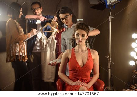 Backstage preparation. Skillful hairdresser is doing hairstyle for young model with joy. Man and woman are working with clothing collection and smiling