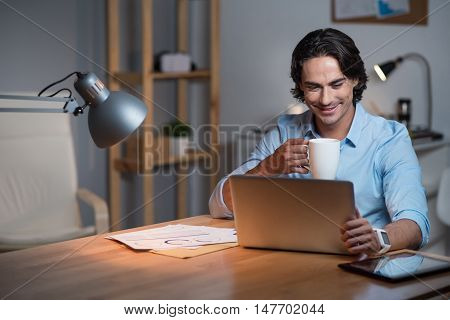 Work with inspiration. Handsome busy young man sitting at the table and drinking tea while using tablet.