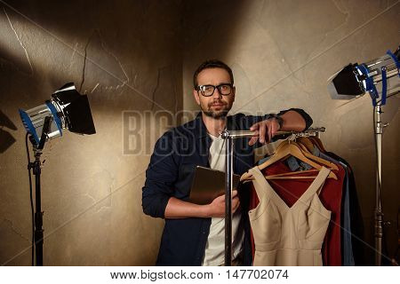 Professional stylist is standing near clothing collection backstage. Man is holding tablet and looking at camera with seriousness