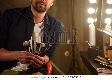 Professional male beautician is holding various make-up brushes. He is sitting near mirror in dressing room