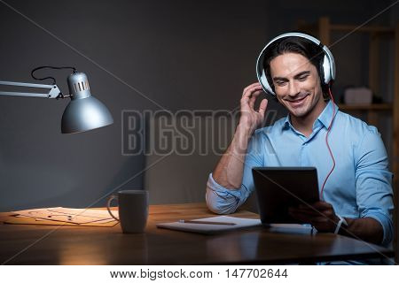Work with fun. Smiling young man using headphones and holding tablet while using listening to music at the table.