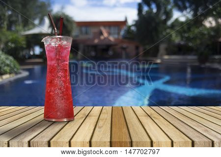 Red soda on Wooden table against of blurred swimming pool. Perspective brown wood over blurred swimming pool,pull your fresh,juice of summer