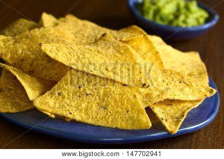 Corn tortilla chips with avocado dip in the back photographed with natural light (Selective Focus Focus on the front edge of the tortilla chip in the middle of the image)