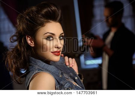 Beautiful young model is standing and posing in studio. She is looking forward with confidence and smiling. Photographer is preparing camera on background