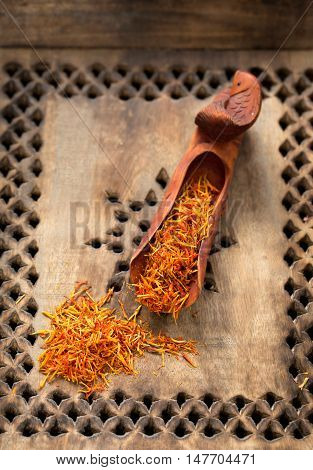 Saffron spice threads in oriental sandalwood handcraft scoop on carved tray closeup