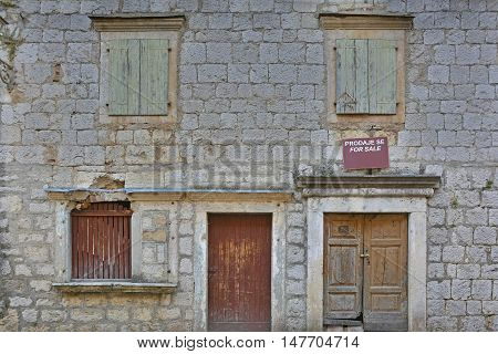 An historic old derelict building in Skradin old town Sibenik-Knin County Croatia. The sign on the wall announces that the building is for sale.