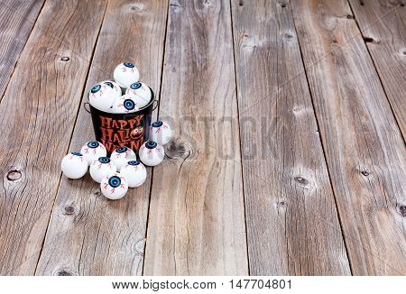 Metal bucket filled with scary eyeballs for Halloween season on rustic wooden boards.