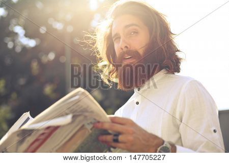 Young man with long hair and beard reading the newspaper