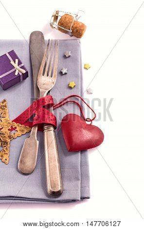 Silverware and red  heart decoration on gray napkin on white