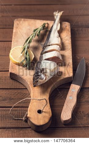 Sliced smoked fish on cutting board and knife