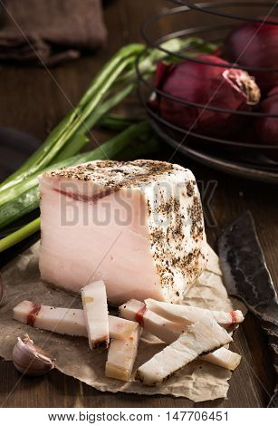 Sliced lard on wooden table with onion and knife