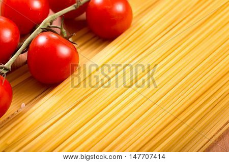 Spaghetti, pasta and cherry tomatoes branch background