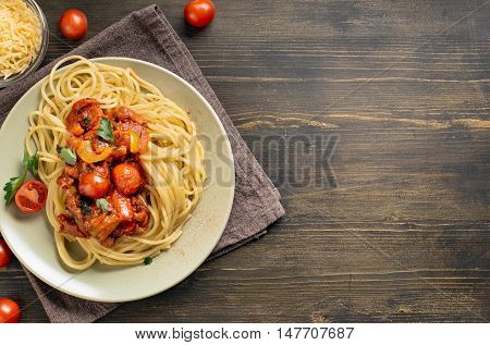 Spaghetti pasta with tomato sauce on wooden table. Top view with copy space