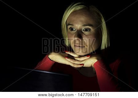 woman working on a computer by night in a dark room with only light from computer falling on her face and her head resting on her hands