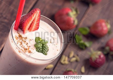 Strawberry lassi with berry close up above