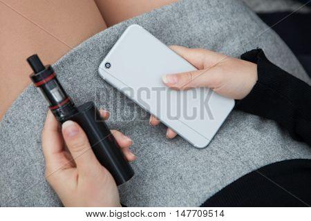 Girl Holding Vaporizer And Modern Smart Phone
