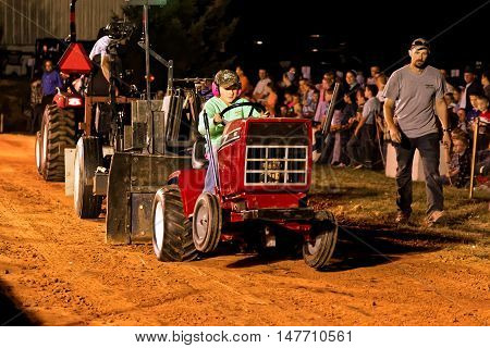 MYERSTOWN, PENNSYLVANIA - SEPTEMBER 16, 2016: A young girl drives a modified lawn tractor at Myerstown East End Days. The tractor pull is an annual community event.