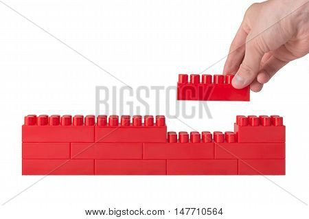 hand holds the last constructor block and completes the wall